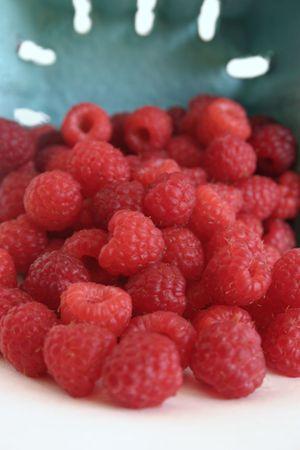 Farm fresh raspberries spilling from carton photo