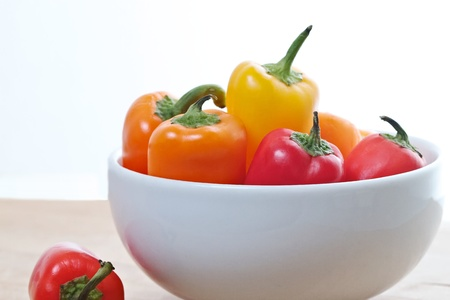 White bowl containing brightly colored mini sweet peppers