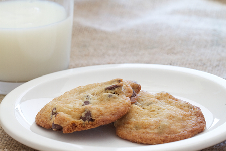 Two homemade chocolate chip cookies and a glass of milk