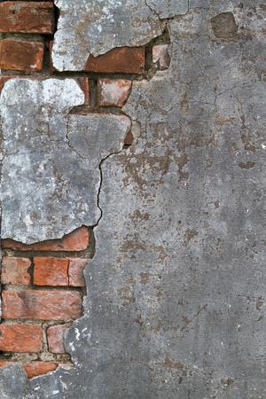 아래 벽돌 레이어를 드러내는 깨진 콘크리트