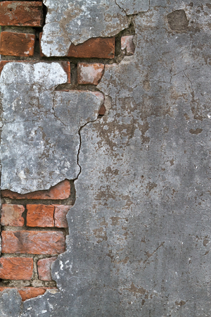 Cracked concrete revealing a brick layer below Stock Photo