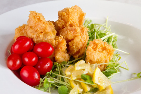 A meal of fried shrimp and cherry tomatoes
