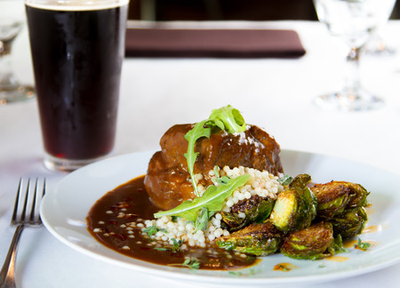 braised: Plates braised pork shoulder with couscous and brussell sprouts