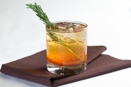 A cocktail in a rocks glass with a rosemary garnish Stok Fotoğraf