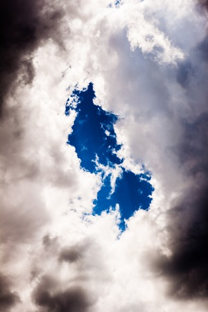 Blue dark hole in sky with clouds photo