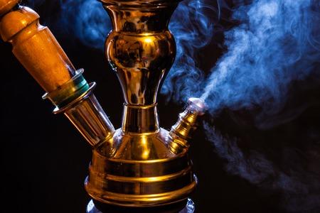 Water pipe hookah with blue smoke photo