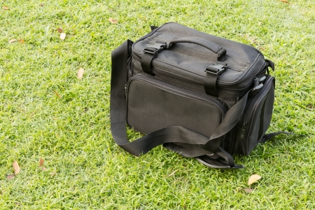 Camera bag in black color on green grass