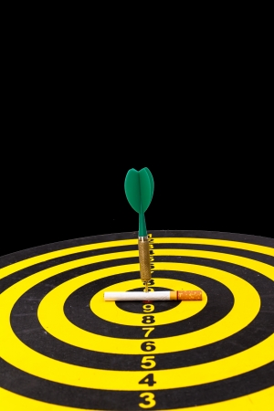 Green darts target to stop smoking concept on black Stock Photo