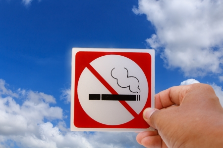 Concept of no smoking symbol on blue sky background photo