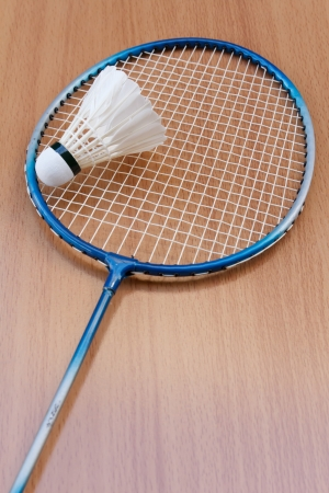 badminton racket and shuttlecock on wooden background photo