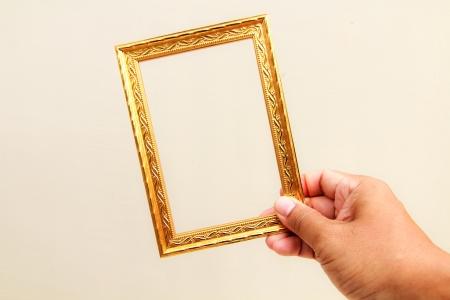 手が白い背景にゴールド フレームを表示します。 写真素材