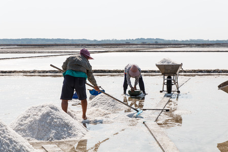 pan tropical: Salt pan and woman worker working on day time, salt pile in Thailand Stock Photo