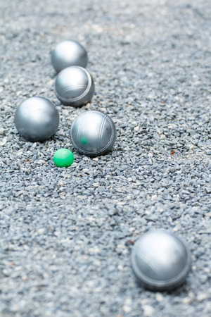 Metallic petanque balls and the small green jack on the ground Standard-Bild