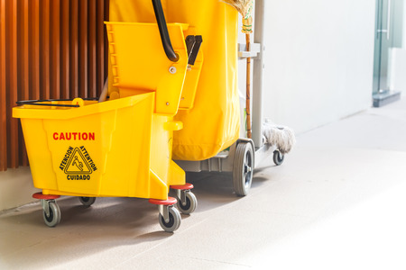 janitorial: Mop bucket and wringer with caution sign on the floor in office building