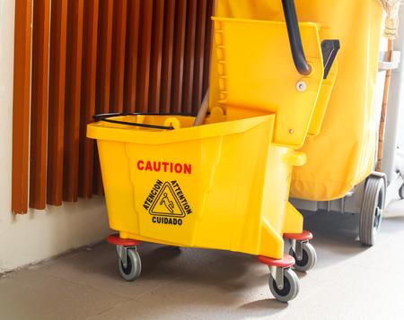 señales de seguridad: Cubo de fregona y escurridor con signo de precaución en el piso en el edificio de oficinas