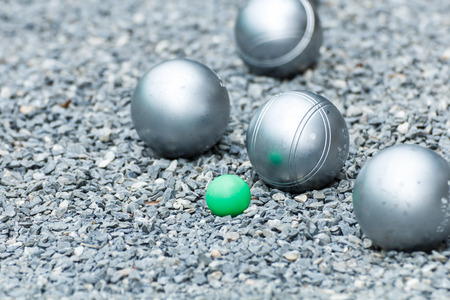 Metallic petanque ball and the small green jack on the ground