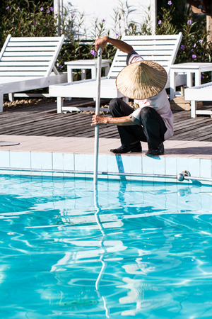 Worker cleaning the pool in morning-3 Reklamní fotografie