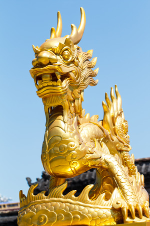 blue dragon: Golden dragon statue with blue sky background Stock Photo