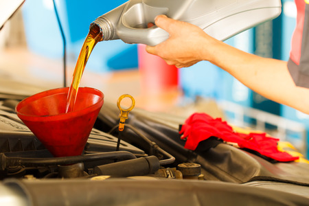Man hand changing motor oil to engine with selective focus photo