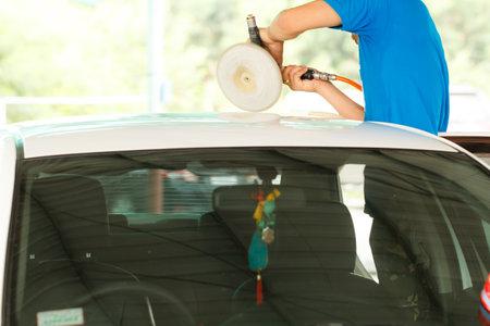 car repair shop: Hands with orbital polisher in auto car repair shop