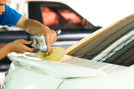 Hands with orbital polisher in auto car repair shop