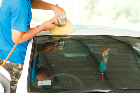 Worker with orbital polisher in auto car repair shop