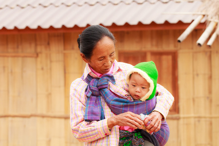 THAILAND-DECEMBER 17, 2014: Unidentified mother Lahu tribe is proudly presenting his baby in the village of bann Jabusi, Chiang Rai province, Thailand.