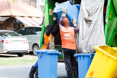 container recycling: Two urban workers municipal recycling garbage collector truck loading waste and trash bin Stock Photo