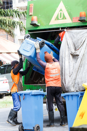 environmental sanitation: Two urban workers municipal recycling garbage collector truck loading waste and trash bin Stock Photo