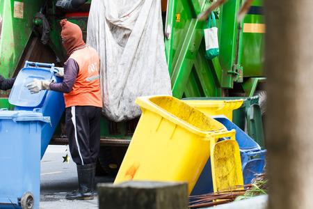 recolector de basura: Trabajador urbano reciclaje de residuos municipales cami�n recolector de basura de carga y contenedor de basura Foto de archivo