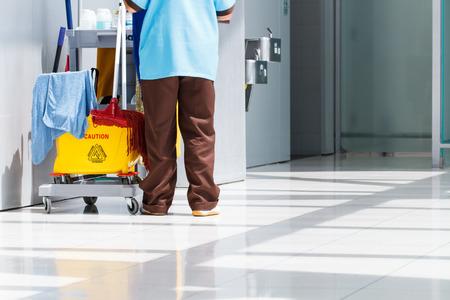 personal de limpieza: Cubo de fregona de limpieza en proceso y trabajador Foto de archivo