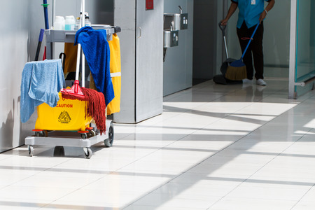 de higiene: Cubo de fregona de limpieza en proceso y trabajador de fondo