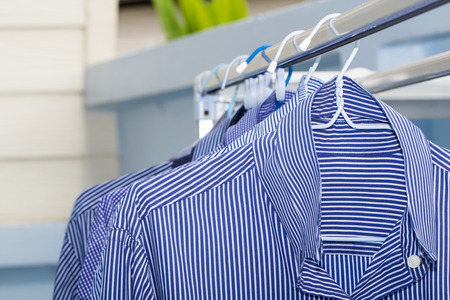 drycleaning: Blue shirt wait for dry during daytime
