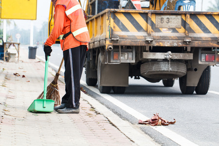 Women worker cleaning road and garbage car background