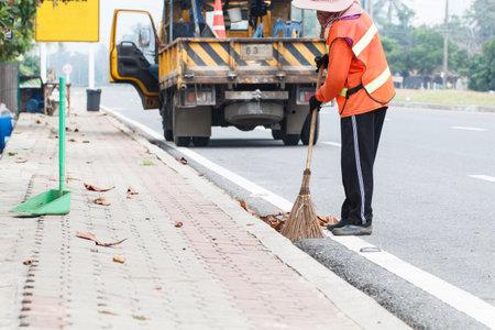 garbage collector: Satun, Tailandia-27 de agosto 2015: contenedor de basura azul con el trabajador de la limpieza del fondo del camino. Foto de la carretera local Satun, Tailandia