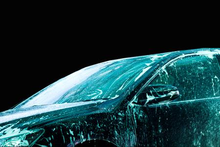 auto lavado: Coche para lavar en el tren de lavado con fondo negro Foto de archivo