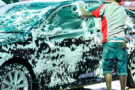 autolavado: Trabajador de lavado de coches en el tren de lavado Foto de archivo