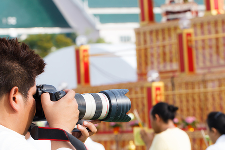 equipping: Young photographer man upholds his camera while shooting candid photo Stock Photo