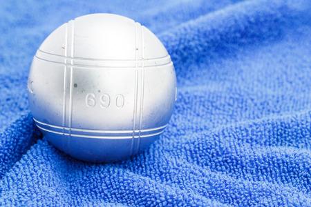 petanque: Metallic petanque ball on the blue background Stock Photo