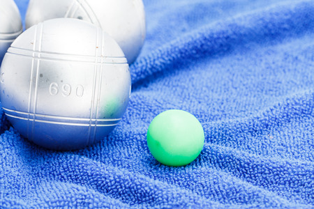 petanque: Metallic petanque ball and the small green jack on the blue background-2