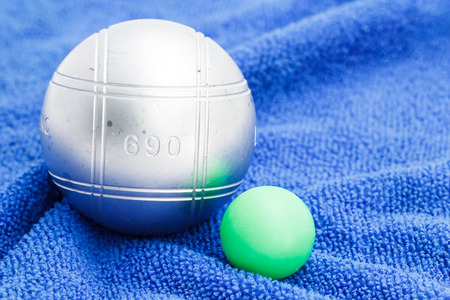 Metallic petanque ball and the small green jack on the blue background