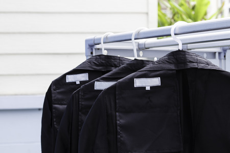 black pants: row of black pants cleaning hangs in wardrobe at home Stock Photo