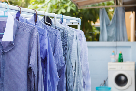 drycleaning: Blue clothes wait for dry with washing machine background-3 Stock Photo