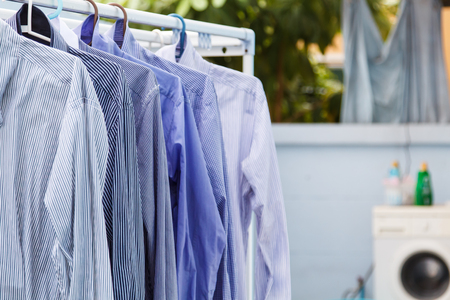 drycleaning: Blue clothes wait for dry with washing machine background-5 Stock Photo