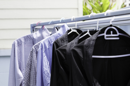 black pants: row of black pants and shirts cleaning hangs in wardrobe