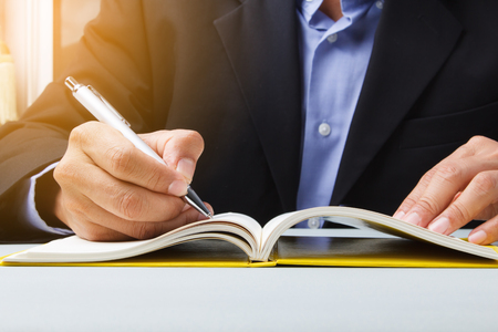 Close-up of Suited man writing schedule dairy book