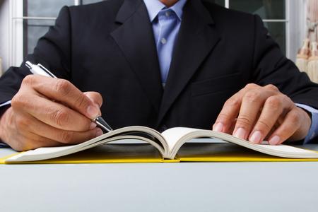 hombre de negocios por escrito el plan de trabajo en el diario con la pluma en el escritorio