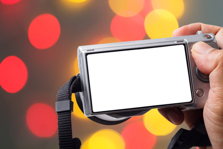 SLR camera in hand with bokeh background