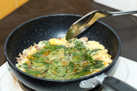 Omelet with spinach herb cooking in olive oil