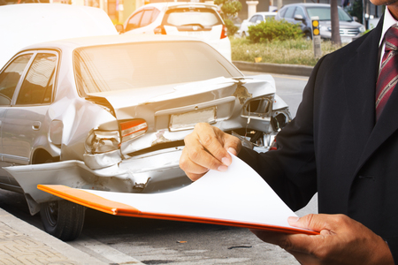 man writing on clipboard while insurance agent examining car after accident